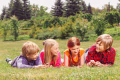 Upbeat children lying on grass in raw Royalty Free Stock Photo