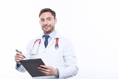 Upbeat doctor holding the folder Royalty Free Stock Images