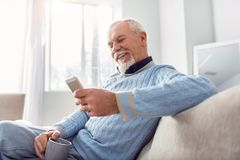 Upbeat elderly man texting while drinking coffee. Good morning. Cheerful elderly man sitting comfortably on the sofa and texting his children while drinking Stock Photo