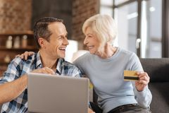 Upbeat elderly mother and son discussing online shopping. Making decisions. Cheerful elderly lady and her young son doing online shopping and discussing the Royalty Free Stock Images