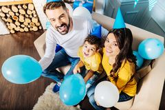 Upbeat family sitting on sofa and holding balloons Stock Photo
