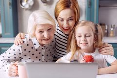 Upbeat females calling someone via laptop. Family call. Three generations of females sitting at the kitchen counter and smiling at the web camera while having a Stock Photo