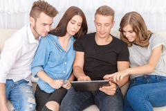 Upbeat friends holding laptop Royalty Free Stock Photos