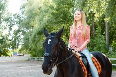 Upbeat girl riding the horse Royalty Free Stock Image