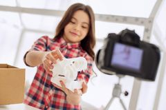 Upbeat girl showing dinosaur skull model to the camera. Check it out. Joyful pre-teen girl showing a dinosaur skull model to the camera while recording an stock photography