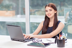 Upbeat girl sitting with laptop Royalty Free Stock Photography