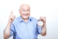 Upbeat grandfather holding alarm clock Stock Photos