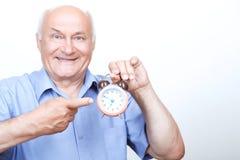 Upbeat grandfather holding alarm clock Stock Images