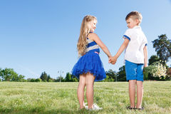 Upbeat little kids holding theur hands together Royalty Free Stock Photo