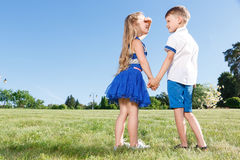 Upbeat little kids holding theur hands together Stock Photos