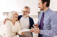Upbeat old couple consulting with financial adviser at home. Consulting with professional. Friendly optimistic harmonious senior couple meeting with financial Royalty Free Stock Photography