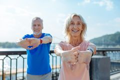 Upbeat senior couple working out in the streets. Effective warm-up. Joyful energetic senior men and women holding hands in a lock and stretching while warming-up Royalty Free Stock Photos