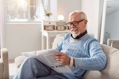 Upbeat senior man smiling while reading article in newspaper. Hilarious content. Pleasant elderly men in eyeglasses reading an article in the newspaper and stock images