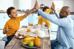 Upbeat single-parent family high-fiving each other at breakfast. Best team. Cheerful single-parent family sitting at the kitchen table and giving each other a Stock Photos