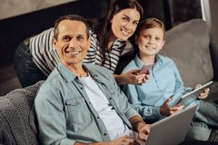 Cheerful family posing while using their gadgets. Upbeat users. Joyful young family sitting on the couch and smiling at the camera, posing while using their Stock Photography