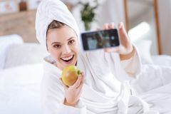 Upbeat woman taking selfie with apple after shower Royalty Free Stock Image