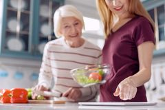Upbeat women checking salad recipe on tablet. Helpful device. The focus being on the hand of a pleasant young women checking a recipe on the tablet while making Stock Photos