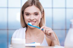 Upbeat young woman brushing her teeth Royalty Free Stock Images