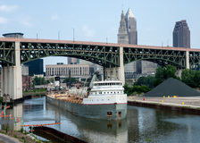 Upbound On The Cuyahoga. A Great Lakes self-discharging bulk carrier ship moves carefully under the Hope Memorial Bridge in Cleveland, Ohio. The ship will stock photos