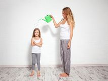 Upbringing child. Family. Upbringing child. Woman pours a child from a watering can. Nurture kids royalty free stock photography