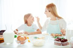 Upbringing forms tasty fooling yummy event joke forefinger point. Ing concept. Cheerful lovely mommy and small playful cute tender girl making sweets and cookies Stock Image