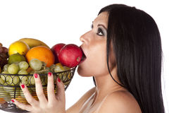 Upclose woman eating from fruit basket Royalty Free Stock Images