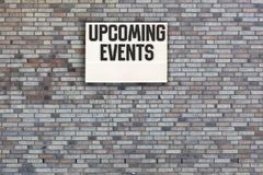 Upcoming Events message on Brick wall with light box. Upcoming Events message in light box on brick wall background for marketing message stock photography