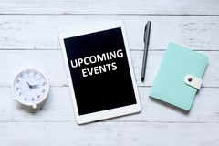 Upcoming events. Top view of table clock,pen,notebook, and tablet computer written with & x27;UPCOMING EVENTS& x27; on white wooden background stock images