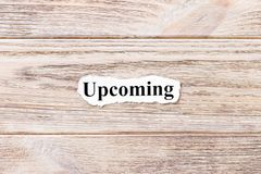 Upcoming of the word on paper. concept. Words of Upcoming on a wooden background.  Royalty Free Stock Photo
