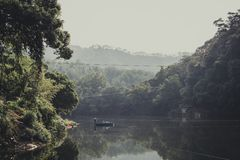 Upcountry of China with man stroke boat in mountain forest view. Old day, old view in upcountry of China with man stroke boat in mountain forest view Stock Photo