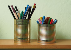 Upcycling, Writing Accessories in Tin Can. Crayons and pens in waste tin cans standing on a shelf Royalty Free Stock Images