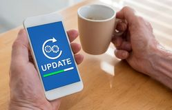 Update concept on a smartphone. Male hands holding a smartphone with update concept and a cup of coffee royalty free stock photos