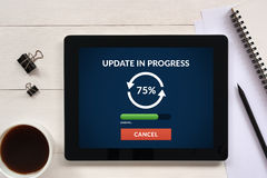 Update concept on tablet screen with office objects on white woo Royalty Free Stock Image