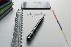 Update - handwritten text in a notebook on a desk. Project update checklist. Notebook, pen and books stock photography