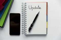 Update - handwritten text in a notebook on a desk. Project update checklist. Notebook, pen and books royalty free stock photo