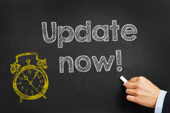 Update now!. Hand writes Update now! on blackboard royalty free stock image