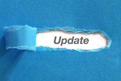 Update. Text appearing behind blue color paper royalty free stock photography