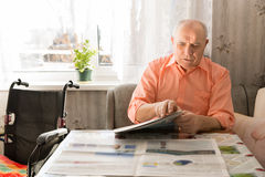 Updated Senior Man Reading Newspaper at the Table Royalty Free Stock Images
