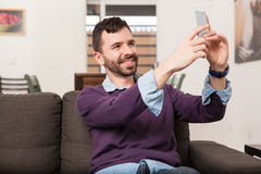Updating my profile picture. Happy young man with a beard taking a selfie for his social media profile picture with his smartphone Stock Photography