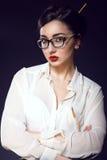 戴updo头发佩带的白色丝绸女衬衫和时髦眼镜的年轻美丽的性感的企业夫人 免版税图库摄影