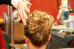 Updo hairstyle. Attractive young Caucasian blonde woman having hair styled for special event Stock Image
