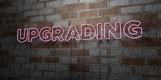 UPGRADING - Glowing Neon Sign on stonework wall - 3D rendered royalty free stock illustration Royalty Free Stock Images