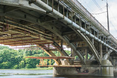 Upgrading and repair of the automobile bridge over the river. Low angle shot from the ground under the bridge. wooden scaffolding Stock Image