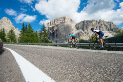 Uphill cycling man is following woman. A couple take a road trip in the dolomites Royalty Free Stock Photography