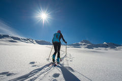 Uphill girl with seal skins and ski mountaineering. On the alps Royalty Free Stock Photography