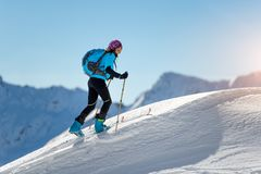 Uphill girl with seal skins and ski mountaineering. On the alps Royalty Free Stock Photos