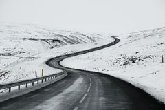 Uphill Road Landscape In Winter At Iceland. Asphalt Road With Sideways Full Of Snow Stock Photo
