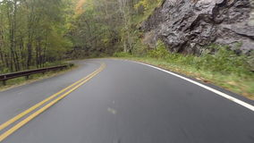 Uphill With Rock on Right on BRP. Climbing uphill on the Blue Ridge Parkway along a rock face stock video footage