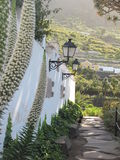 Uphill street with flowers and lamps in Tenerife, Spain Royalty Free Stock Photography