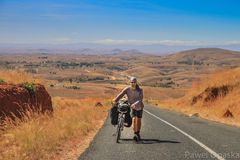 Uphill struggle. Man pushing his bike uphill on a steep road in Central Madagascar Stock Image